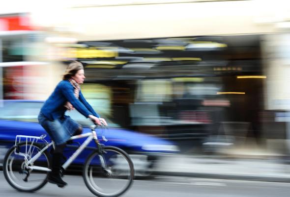 Woman Cycling in City Street