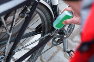 Person lubicating bike chain